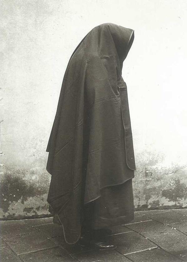 Vrouw gehuld in regenkleed of falie, Stein